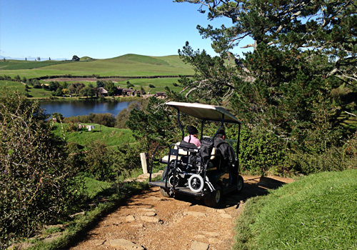 Mobility impaired traveller taking a tour of Lord of the Rings movie set, Hobbiton
