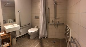 Disabled access bathroom with roll in shower, pull down bench seat, hand rails by shower and toilet