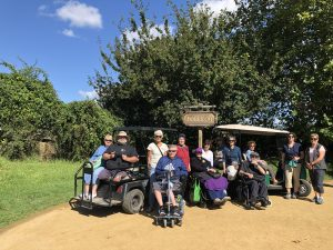 Wheelchair travelling group at entrance to Hobbiton