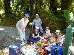 family group enjoying a picnic in the bush